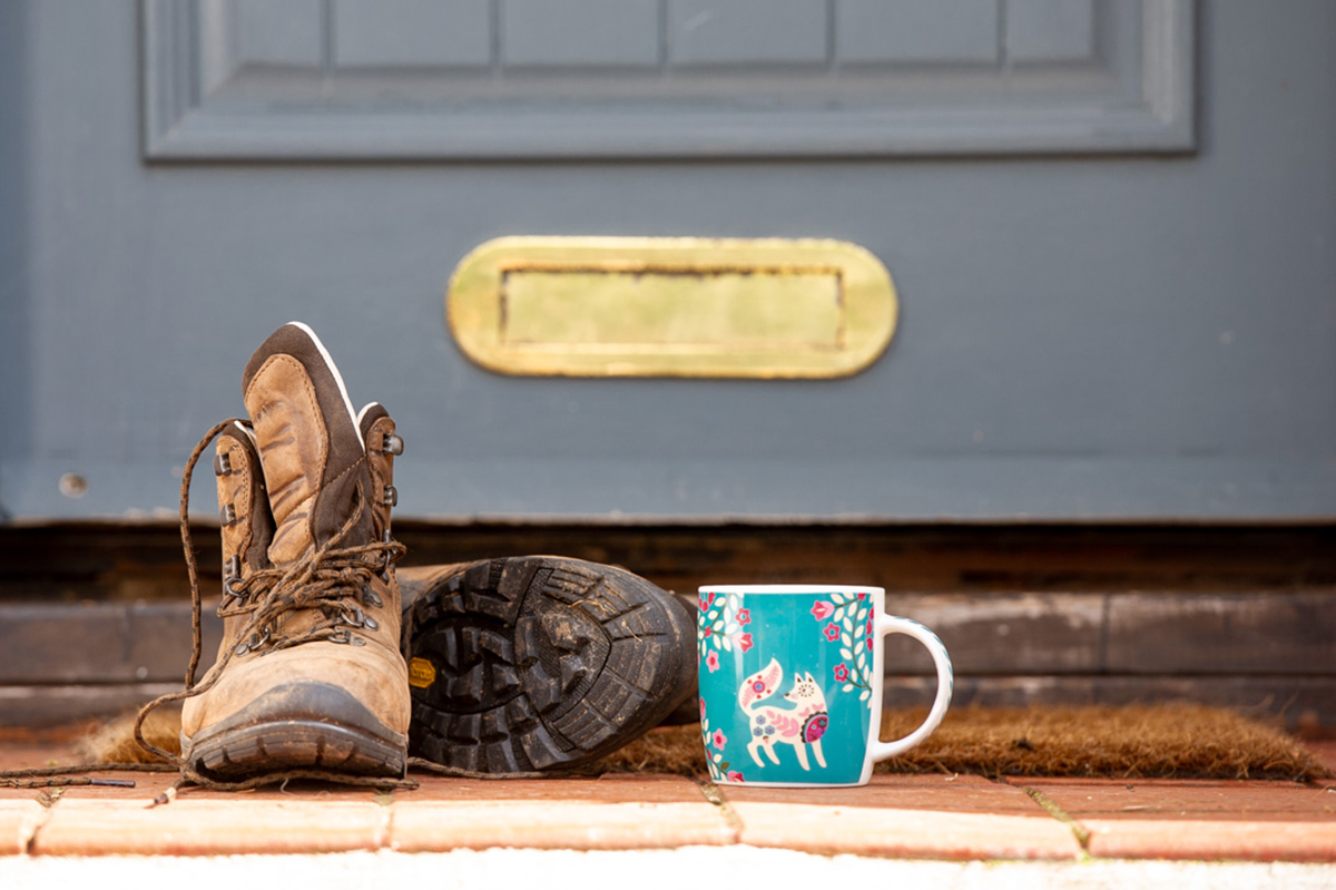 Boots and mug at front door of a country home